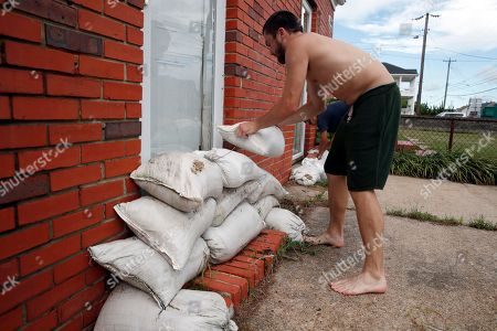 Adam Bazemore, Sebastian Silva. Adam Bazemore places sandbags in the doorways, in the Willoughby Spit area of Norfolk, Va., as he makes preparations for Hurricane Florence