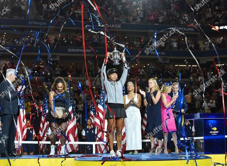 Naomi Osaka of Japan holds up the trophy as runner-up Serena Williams (2nd L) of the United States, USTA President Katrina Adams (4th R), JPMorgan Chase CMO Kristin Lemkau (3rd R), and Chris Evert (2nd R) look on during the award ceremony