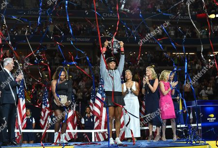Stock Picture of Naomi Osaka of Japan holds up the trophy as runner-up Serena Williams (2nd L) of the United States, USTA President Katrina Adams (4th R), JPMorgan Chase CMO Kristin Lemkau (3rd R), and Chris Evert (2nd R) look on during the award ceremony