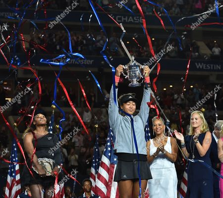 Naomi Osaka of Japan holds up the trophy as runner-up Serena Williams (L) of the United States, USTA President Katrina Adams (2nd R), and JPMorgan Chase CMO Kristin Lemkau (R) look on during the award ceremony