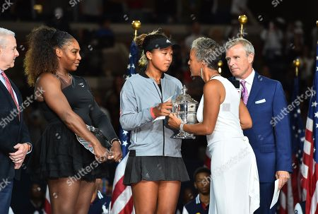 Stock Photo of Naomi Osaka of Japan receives the trophy from USTA President Katrina Adams as runner-up Serena Williams of the United States looks on during the award ceremony