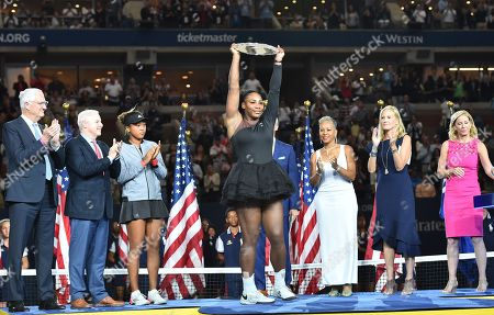 Serena Williams of the United States holds up her runner-up trophy as winner Naomi Osaka (3rd L) of Japan, USTA President Katrina Adams (3rd R), JPMorgan Chase CMO Kristin Lemkau (2nd R), and Chris Evert (R) look on during the award ceremony