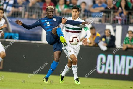 USA forward Gyasi Zardes (L) and Mexico defender Hugo Ayala (R) go after the ball in the first half of their friendly soccer match at Nissan Stadium in Nashville, Tennessee, USA, 11 September 2018.
