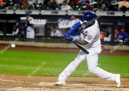 New York Mets' Jose Reyes hits an RBI double during the second inning of a baseball game against the Miami Marlins, in New York