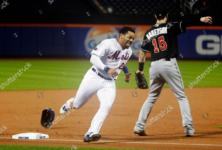 New York Mets' Dominic Smith (22) runs past Miami Marlins' Brian Anderson to score on a double by Jose Reyes during the second inning of a baseball game, in New York