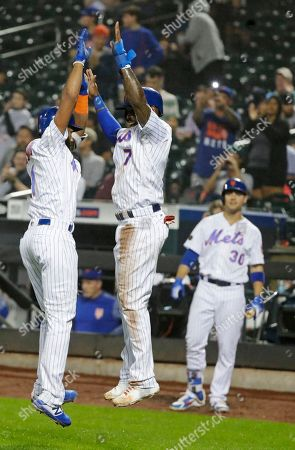 New York Mets' Amed Rosario, left, celebrates with Jose Reyes, center, as Michael Conforto watches after Rosario hit a three-run home run during the fourth inning of a baseball game against the Miami Marlins, in New York