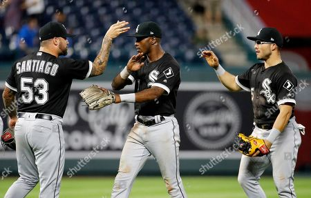 Chicago White Sox's Hector Santiago (53), Tim Anderson, center, and Yolmer Sanchez celebrate after their baseball game against the Kansas City Royals, in Kansas City, Mo. The Chicago White Sox won 4-2 in 12 innings