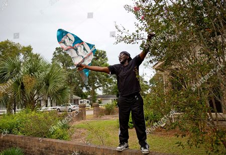 Larry Johnson gets a kite out of a tree while flying it with his neighbor in the calm before Hurricane Florence approaches Myrtle Beach, S.C