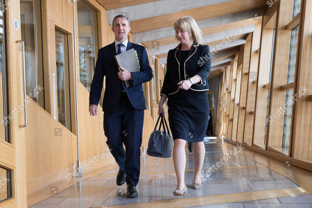Michael Matheson, Cabinet Secretary for Transport, Infrastructure and Connectivity, and Shona Robison make their way to the Debating Chamber.