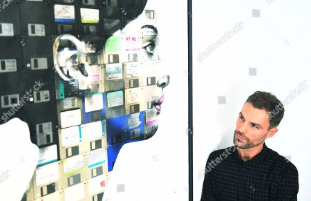British artist, Nick Gentry poses for photographs next to his work entitled Profile number 16, 2018 during a photocall for the Human Connection exhibition at the Opera Gallery in London, Britain, 13  September 2018. Nick Gentry paints portraits on top of obsolete technological materials such as VHS cassettes and floppy disks that contain people's memories. His work is part of a joint exhibition with South Korea artist Seo Young-Deok at the Opera Gallery.