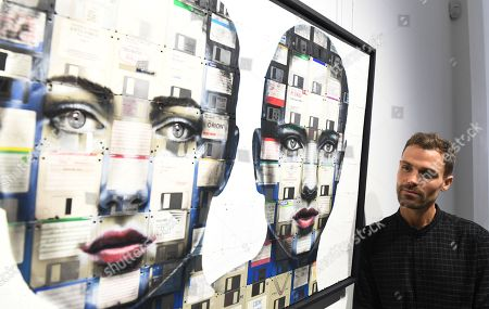British artist, Nick Gentry poses for photographs next to his work entitled Combination 1 during a photocall for the Human Connection exhibition at the Opera Gallery in London, Britain, 13  September 2018. Nick Gentry paints portraits on top of obsolete technological materials such as VHS cassettes and floppy disks that contain people's memories. His work is part of a joint exhibition with South Korea artist Seo Young-Deok at the Opera Gallery.