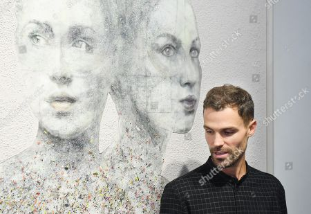 British artist, Nick Gentry poses for photographs next to his work entitled Lifelike, 2018 during a photocall for the Human Connection exhibition at the Opera Gallery in London, Britain, 13  September 2018. Nick Gentry paints portraits on top of obsolete technological materials such as VHS cassettes and floppy disks that contain people's memories. His work is part of a joint exhibition with South Korea artist Seo Young-Deok at the Opera Gallery.
