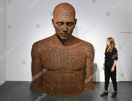 A gallery employee poses next to a bicycle chain sculpture en titled Iron chain (Rust) 2013 by South Korean artist Seo Young-Deok during a photocall for the Human Connection exhibition at the Opera Gallery in London, Britain, 13  September 2018. Nick Gentry paints portraits on top of obsolete technological materials such as VHS cassettes and floppy disks that contain people's memories. His work is part of a joint exhibition with South Korea artist Seo Young-Deok at the Opera Gallery.