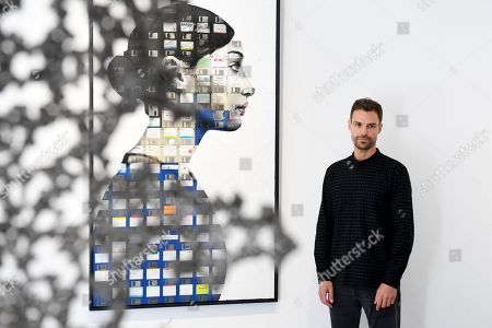 Stock Picture of British artist, Nick Gentry poses for photographs next to his work entitled Profile number 16, 2018 during a photocall for the Human Connection exhibition at the Opera Gallery in London, Britain, 13  September 2018. Nick Gentry paints portraits on top of obsolete technological materials such as VHS cassettes and floppy disks that contain people's memories. His work is part of a joint exhibition with South Korea artist Seo Young-Deok at the Opera Gallery.