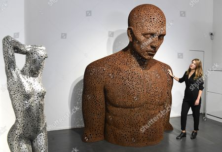 Stock Photo of A gallery employee poses next to a bicycle chain sculpture en titled Iron chain (Rust) 2013 by South Korean artist Seo Young-Deok during a photocall for the Human Connection exhibition at the Opera Gallery in London, Britain, 13  September 2018. Nick Gentry paints portraits on top of obsolete technological materials such as VHS cassettes and floppy disks that contain people's memories. His work is part of a joint exhibition with South Korea artist Seo Young-Deok at the Opera Gallery.
