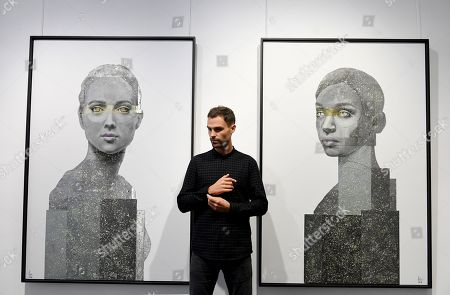 British artist, Nick Gentry poses for photographs next to his work entitled Human Connection (L) and Being 2 (R), 2018 during a photocall for the Human Connection exhibition at the Opera Gallery in London, Britain, 13  September 2018. Nick Gentry paints portraits on top of obsolete technological materials such as VHS cassettes and floppy disks that contain people's memories. His work is part of a joint exhibition with South Korea artist Seo Young-Deok at the Opera Gallery.