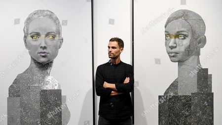 Stock Image of British artist, Nick Gentry poses for photographs next to his work entitled Human Connection (L) and Being 2 (R), 2018 during a photocall for the Human Connection exhibition at the Opera Gallery in London, Britain, 13  September 2018. Nick Gentry paints portraits on top of obsolete technological materials such as VHS cassettes and floppy disks that contain people's memories. His work is part of a joint exhibition with South Korea artist Seo Young-Deok at the Opera Gallery.