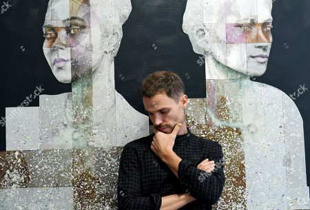 British artist, Nick Gentry poses for photographs next to his work entitled Combination 2, 2018 during a photocall for the Human Connection exhibition at the Opera Gallery in London, Britain, 13  September 2018. Nick Gentry paints portraits on top of obsolete technological materials such as VHS cassettes and floppy disks that contain people's memories. His work is part of a joint exhibition with South Korea artist Seo Young-Deok at the Opera Gallery.