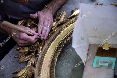A craftsman works on the golden patina of a mirror's frame being restored in one of the workshop of the Mobilier National in Paris, France, 13 September 2018. The Mobilier National is a French service agency depending on the French Ministry of Culture. Administering the Beauvais Manufactory and the Gobelins Manufactory, its role is to preserve, restore, stock pieces of furniture reserved for the national institutions (Elysee Palace, embassies...) but also to create new pieces. For the first time since 1937, the Mobilier National will be open for the public during the Patrimony Days on the 15 and 16 September.