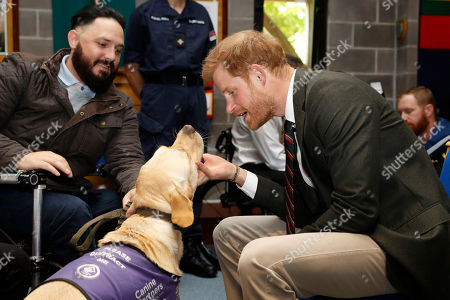Prince Harry speaks with Royal Marine Phil Eaglesham and his dog Cooper, during his visit The Royal Marines Commando Training Centre