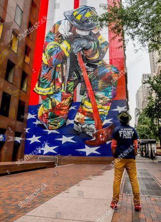Brazilian muralist Eduardo Kobra is seen opposite his work 'The Braves of 9/11'