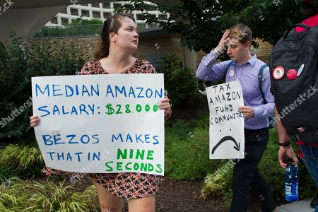Demonstrators protest against Amazon and Jeff Bezos, Amazon founder and CEO, outside of the hotel where the Economic Club of Washington is having their Milestone Celebration in Washington, . Bezos said Thursday that he is giving $2 billion to start the Bezos Day One Fund which will open preschools in low-income neighborhoods and give money to nonprofits that helps homeless families