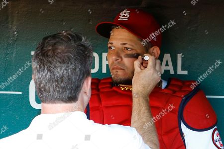 St. Louis Cardinals catcher Yadier Molina, right, has eye black applied by trainer Chris Conroy prior to a baseball game against the Los Angeles Dodgers, in St. Louis
