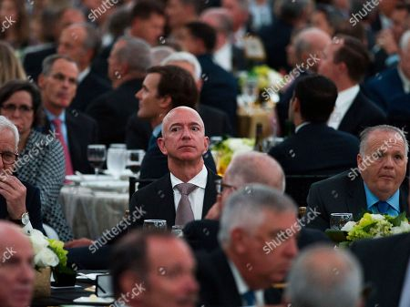 Jeff Bezos, Amazon founder and CEO, center, attends The Economic Club of Washington's Milestone Celebration in Washington, . Bezos said Thursday that he is giving $2 billion to start the Bezos Day One Fund which will open preschools in low-income neighborhoods and give money to nonprofits that helps homeless families