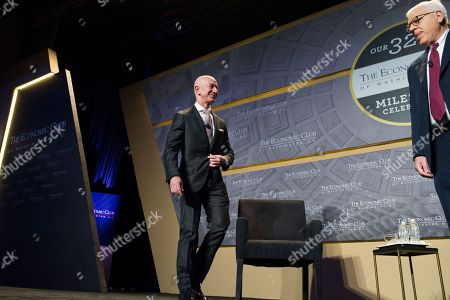 Jeff Bezos, Amazon founder and CEO, left, and David Rubenstein, president, Economic Club of Washington, walk onstage to address the clubs' Milestone Celebration in Washington, . Bezos said Thursday that he is giving $2 billion to start the Bezos Day One Fund which will open preschools in low-income neighborhoods and give money to nonprofits that helps homeless families