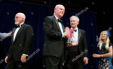 Bruce Blank, John M. Barry, Michel Boileau. John Barrett, center, holds his Ig Nobel award with fellow recipients Bruce Blank, right, and Michel Boileau, left, during ceremonies at Harvard University in Cambridge, Mass., . The men won for using postage stamps to test whether the male sexual organ is functioning properly