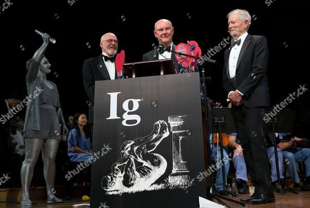 Stock Picture of John Barrett, center, Bruce Blank, right, and Michel Boileau, left, accept the Ig Noble award for reproductive medicine during ceremonies at Harvard University in Cambridge, Mass., . The men won for using postage stamps to test whether the male sexual organ is functioning properly