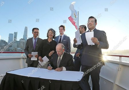 Ed Chau, Nancy Skinner, Henry Stern, Ben Allen, Ricardo Lara, Jerry Brown. Los Angeles area Democrat, State Sen. Ricardo Lara, right displays bills signed by Calif., Gov. Jerry Brown, during a ceremony, in San Francisco. Brown signed the bills, aimed at easing global warming during a cruise aboard the high-tech battery-operated San Francisco Bay sightseeing boat, Enhydra. Along with Lara, Brown was flanked by Democrats, Assemblyman Ed Chau, left, and Senators Nancy Skinner, Henry Stern, third from left and Ben Allen, second from right