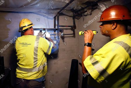 Columbia Gas employee Brian Jones shines a flashlight so his partner, using a wrench, can shut off the gas in a home, in Andover, Mass. Multiple houses were damaged Thursday afternoon from gas explosions and fires triggered by a problem with a gas line that feeds homes in several communities north of Boston
