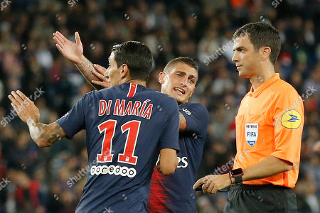 PSG's Angel Di Maria, left, and PSG's Marco Verratti, center, claim a hands ball as they talk to Referee Frank Schneider during their French League One soccer match between Paris-Saint-Germain and Saint-Etienne at the Parc des Princes stadium in Paris