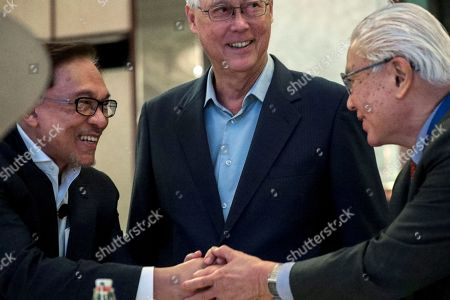 Stock Image of Former Malaysian Deputy Prime Minister Anwar Ibrahim (L) shakes hands with former Singapore President Tony Tan (R) as Singapore Emeritus Senior Minister Goh Chok Tong (C) looks on during the Singapore Summit at the Shangri-La Hotel in Singapore, 15 September 2018. Ibrahim is the chief of Malaysia's ruling coalition party Pakatan Harapan.