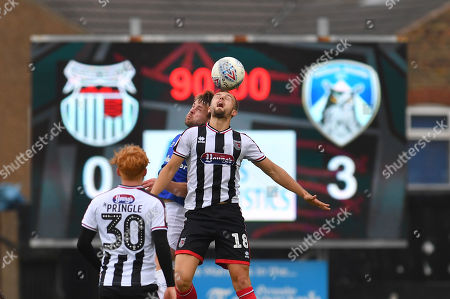 Oldham Athletic defender Andy Taylor (3) and Grimsby Town forward Charles Vernam(18) go for ball just before final whistle with a 0-3 win for Oldham during the EFL Sky Bet League 2 match between Grimsby Town FC and Oldham Athletic at Blundell Park, Grimsby