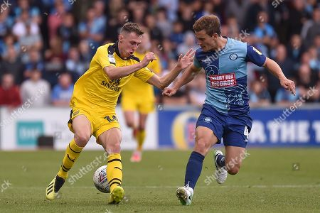 Oxford United midfielder Gavin Whyte (16) battles for possession  with Wycombe Wanderers midfielder Dominic Gape (4) during the EFL Sky Bet League 1 match between Wycombe Wanderers and Oxford United at Adams Park, High Wycombe