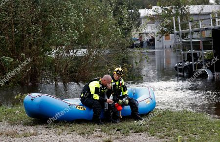 Members of a combined New Bern/Greenville swift water rescue team Brad Johnson, left, and Steve Williams rest after searching for people stranded by floodwaters caused by the tropical storm Florence in New Bern, N.C., on