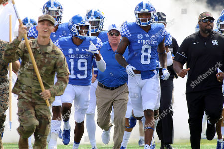 Kentucky Wildcats coach Mark Stoops (center) leads his team onto the field with Akeem Hayes (19) and Danny Clark (8) prior to an NCAA football game between the Kentucky Wildcats and the Murray State Racers at Kroger Field in Lexington, Kentucky