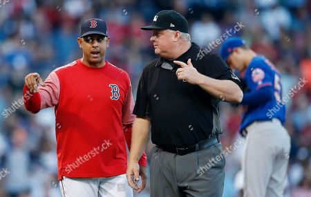 Boston Red Sox manager Alex Cora, left, talks to first base umpire Bill Miller after an overruled call on Jackie Bradley Jr. during the fifth inning of a baseball game against the New York Mets in Boston