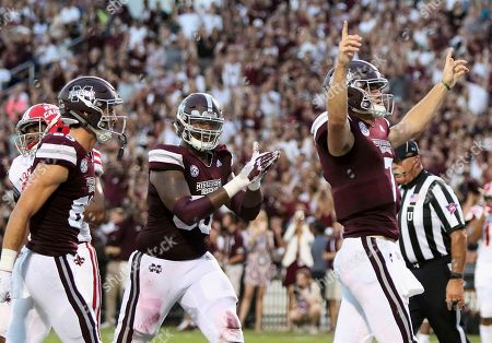 Mississippi State quarterback Nick Fitzgerald (7) celebrates his first touchdown of the day as teammates Austin Williams, left, and Greg Eiland, center, come in to congratulate him during the first half of their NCAA college football game against Louisiana-Lafayette, in Starkville, Miss