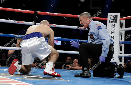 Referee Russell Mora counts to Gary O'Sullivan before stopping the fight in the first round during a middleweight boxing match against David Lemieux, in Las Vegas. Lemieux won by TKO