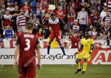 FC Dallas forward Dominique Badji (16) heads the ball as Columbus Crew defender Jonathan Mensah (4) defends and FC Dallas' Reto Ziegler (3) looks on during the first half of an MLS soccer match, in Frisco, Texas
