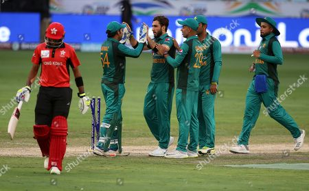 Usman Khan, Tanvir Afzal. Pakistan's Usman Khan, center without cap, celebrates with teammates the dismissal of Hong Kong's Tanvir Afzal, left, during the one day international cricket match of Asia Cup between Pakistan and Hong Kong in Dubai, United Arab Emirates