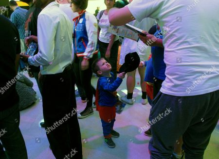 """A boy dressed as Superman stands among other visitors to the Comic Con Africa event, a three-day comic book and pop culture convention in Johannesburg, South Africa, on . Wonder Woman and other usual superheroes were in abundance, but also some African characters seemingly sparked by the success of Marvel's """"Black Panther"""" film"""