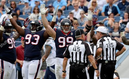 Houston Texans defensive end J.J. Watt (99) and defensive end Joel Heath (93) hope for a touchdown call from officials in the second half of an NFL football game against the Tennessee Titans, in Nashville, Tenn. Possession of the ball was given back to the Titans on the play