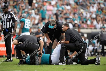 Jacksonville Jaguars head coach Doug Marrone, center, looks on as offensive tackle Cam Robinson (74) is helped by trainers after suffering an injury while blocking New England Patriots defensive end Adrian Clayborn as Jaguars quarterback Blake Bortles threw a pass during the first half of an NFL football game, in Jacksonville, Fla