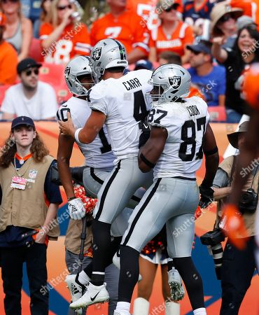 Oakland Raiders wide receiver Seth Roberts (10) celebrates his touchdown with quarterback Derek Carr (4) and tight end Jared Cook (87) during the second half of an NFL football game against the Denver Broncos, in Denver