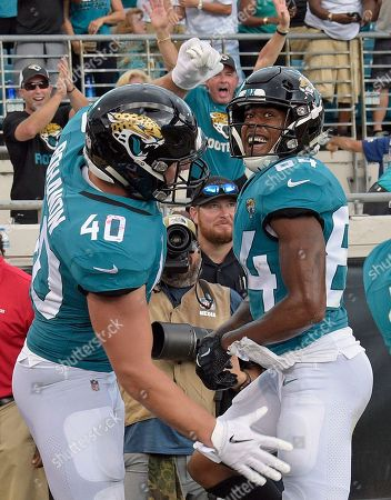 Jacksonville Jaguars wide receiver Keelan Cole, right, celebrates a touchdown catch against the New England Patriots with running back Tommy Bohanon (40) during the first half of an NFL football game, in Jacksonville, Fla