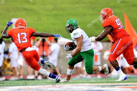 Stock Photo of North Dakota Fighting Hawks running back Brady Oliveira (5) is pursued by Sam Houston State Bearkats defensive back Daniel Adams (13) and Sam Houston State Bearkats defensive lineman Brandon Jackson Jr. (93) during a NCAA football game between the University of North Dakota Fighting Hawks and Sam Houston State Bearkats at Elliott T. Bowers Stadium in Huntsville, Texas. North Dakota defeated Sam Houston State 24 -23